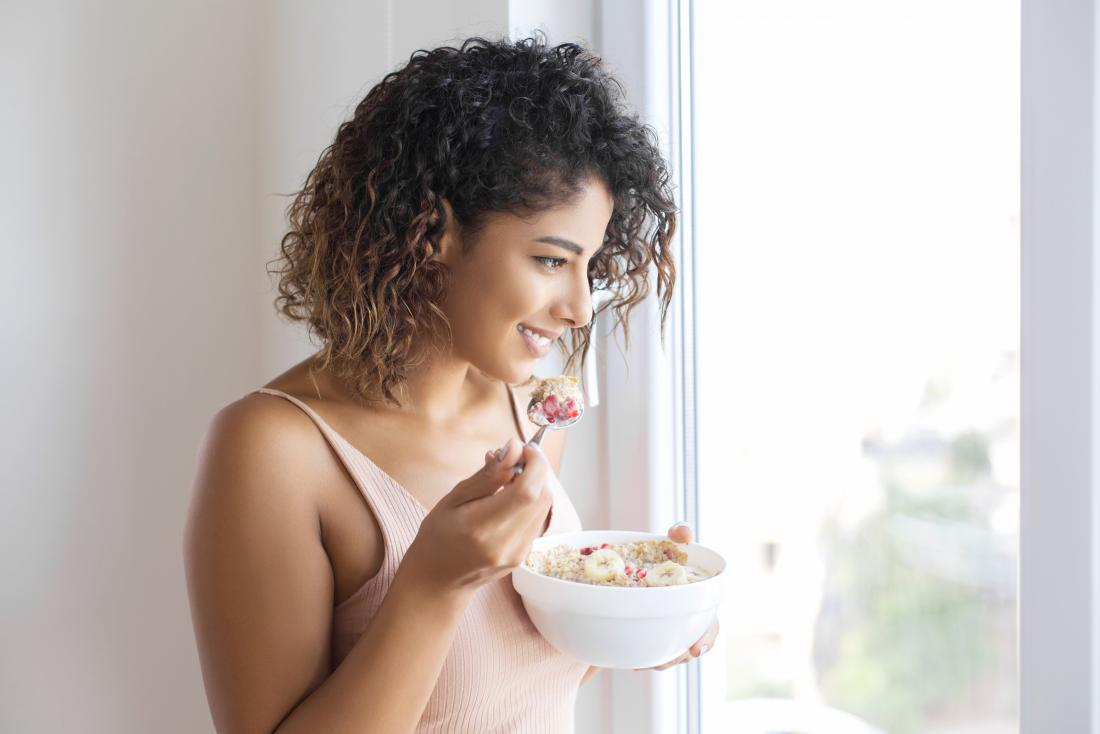 a woman looking out the window whilst eating some low fat foods
