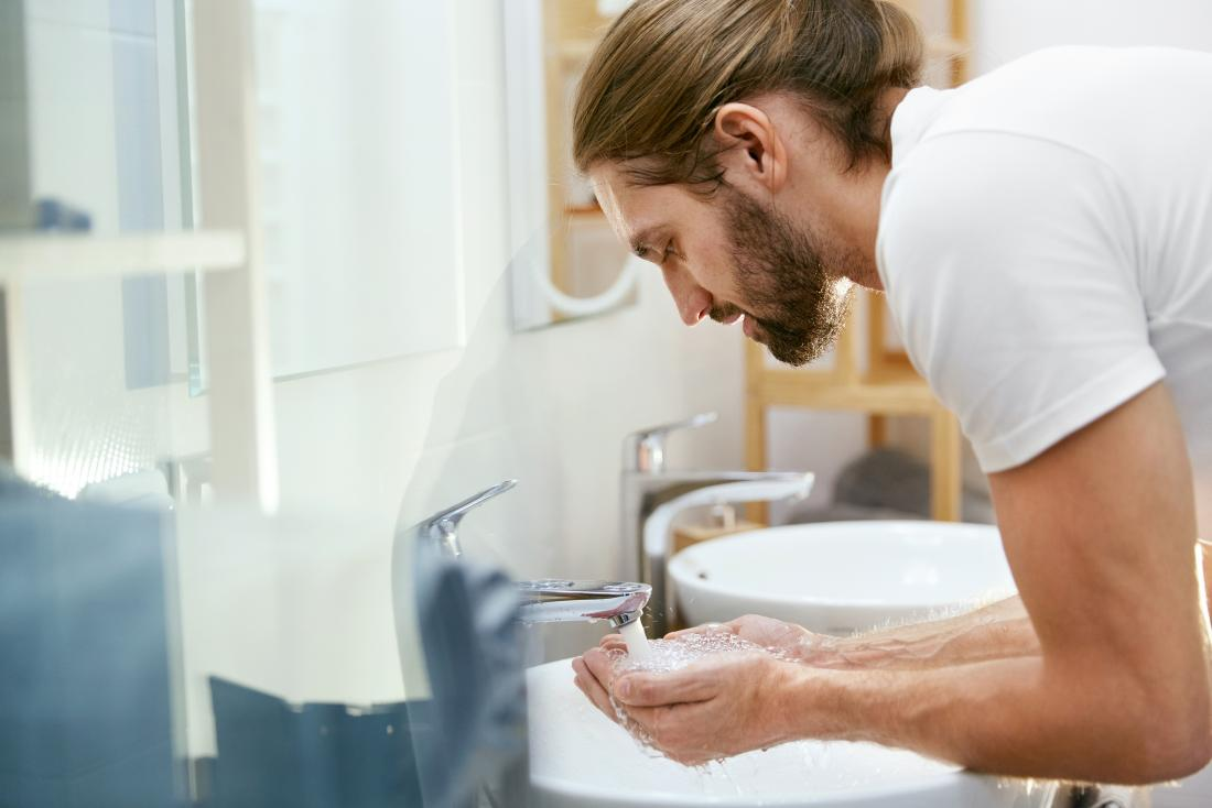 a bearded man about to wash his face with water.