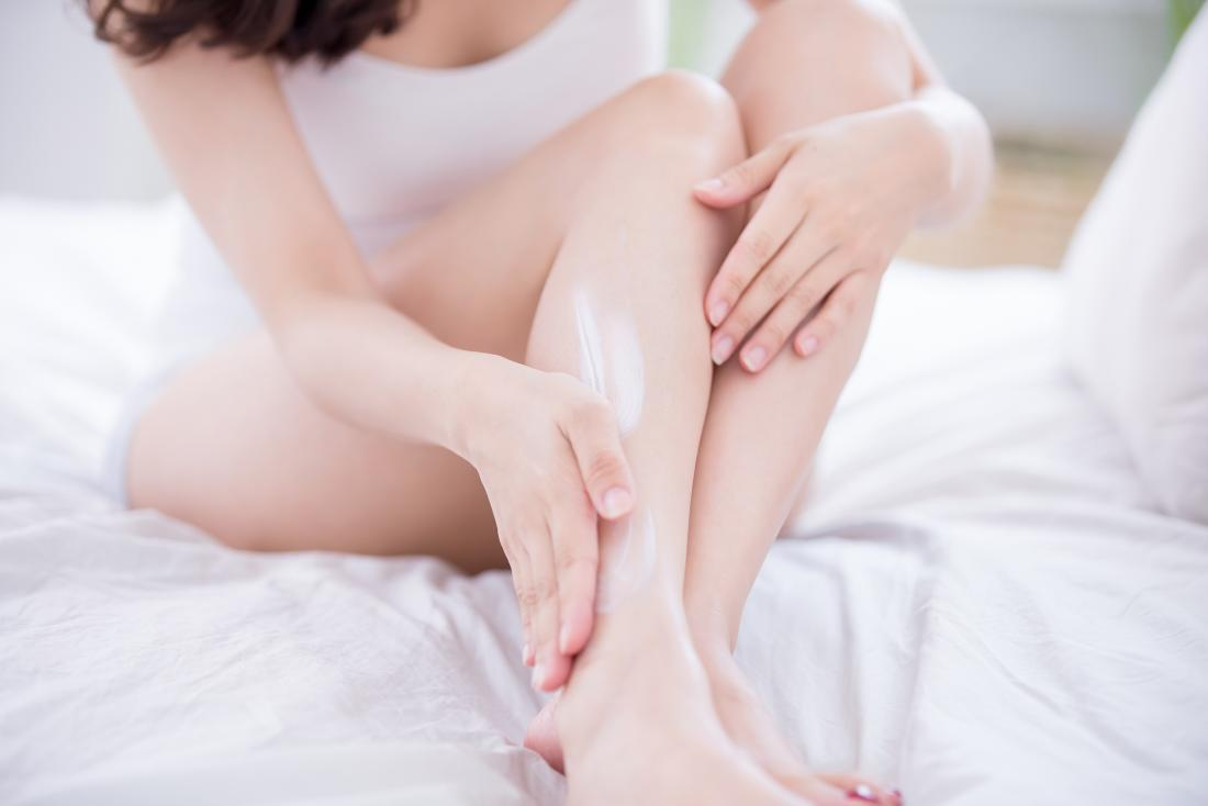 A woman applying lotion to her leg on her bed.