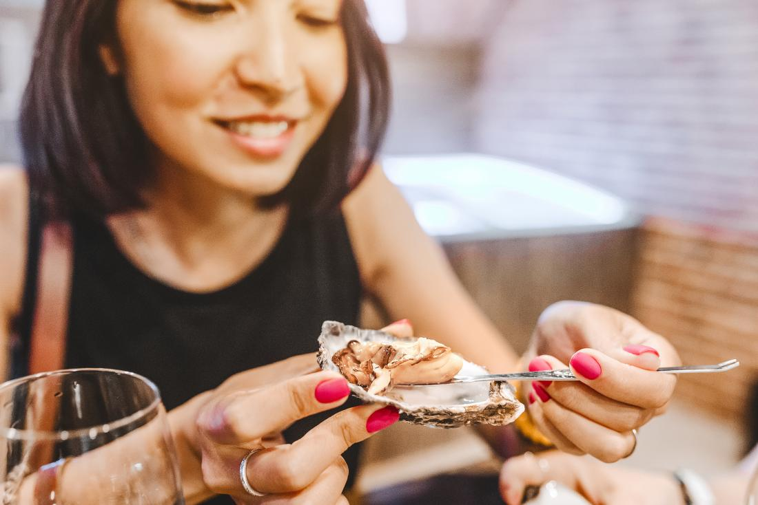 A woman eating oysters which are among the Foods high in zinc