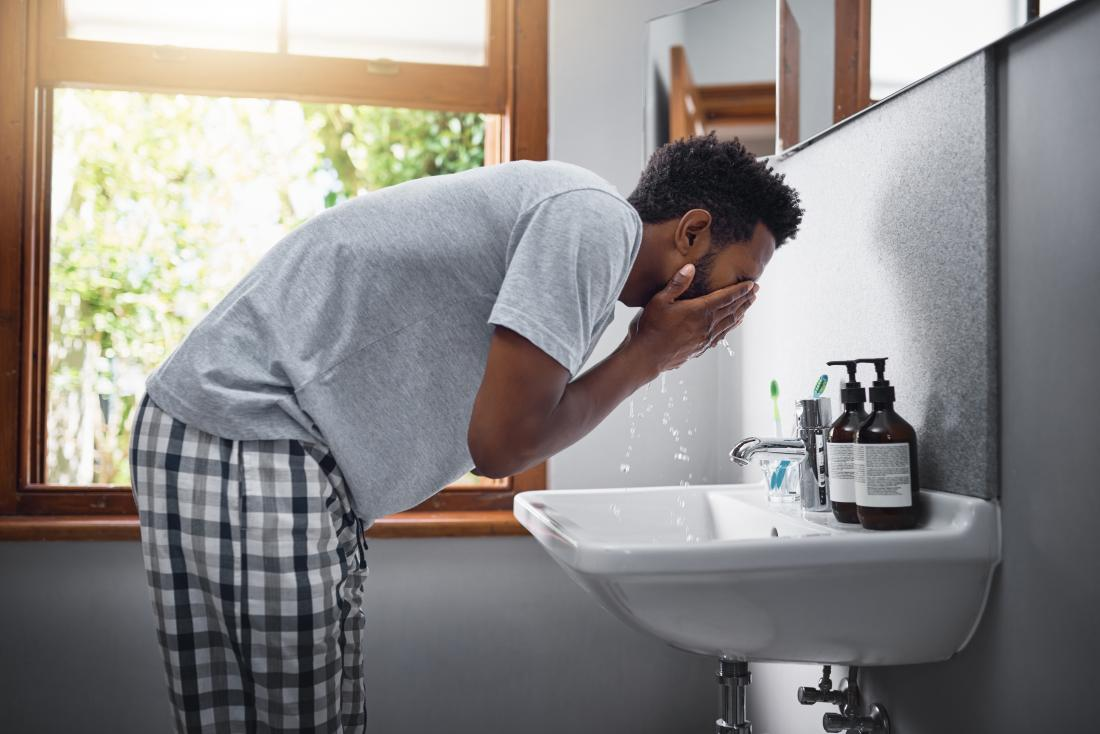 a man washing his face in the sink whilst the weather is lovely outside