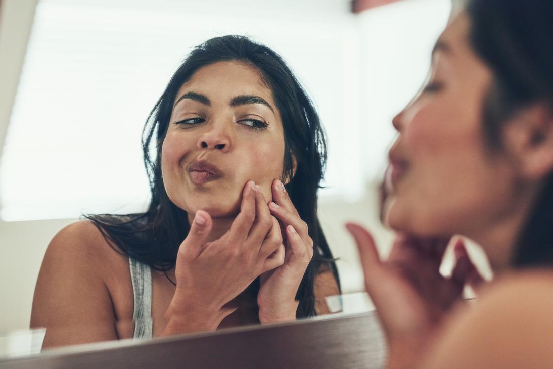 uma mulher olhando acne na bochecha.