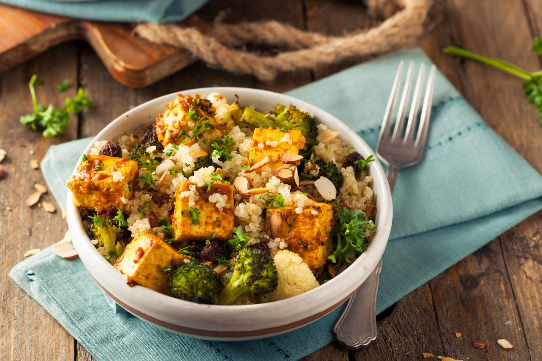 homemade quinoa tofu bowl with broccoli vegan meal on wooden table with blue rustic napkins