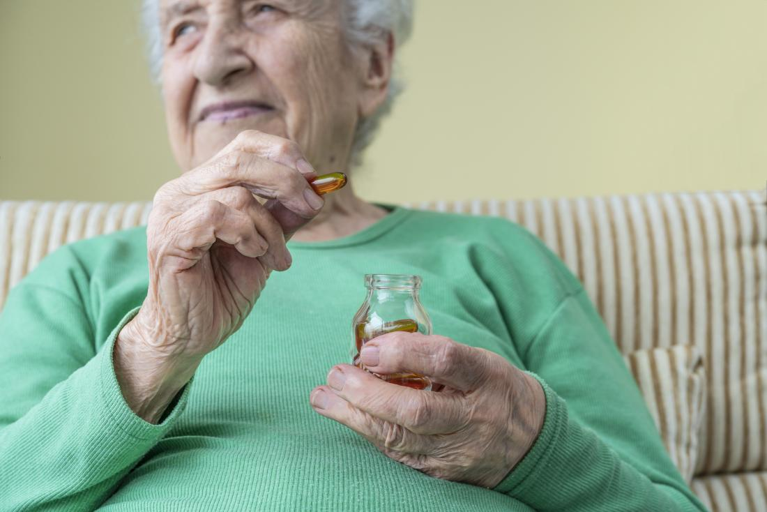 A woman taking a omega 3 capsule as part of a Anti inflammatory supplements plan