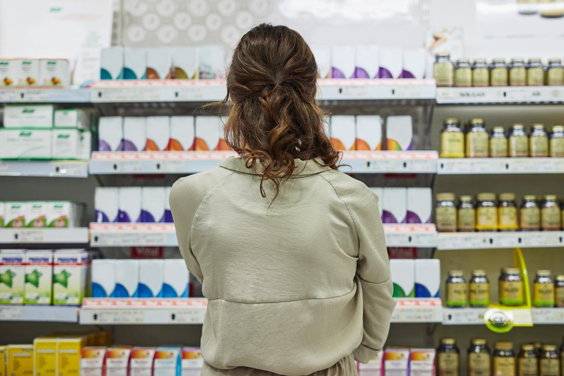 a woman deciding what to buy from a pharmacy shelve.