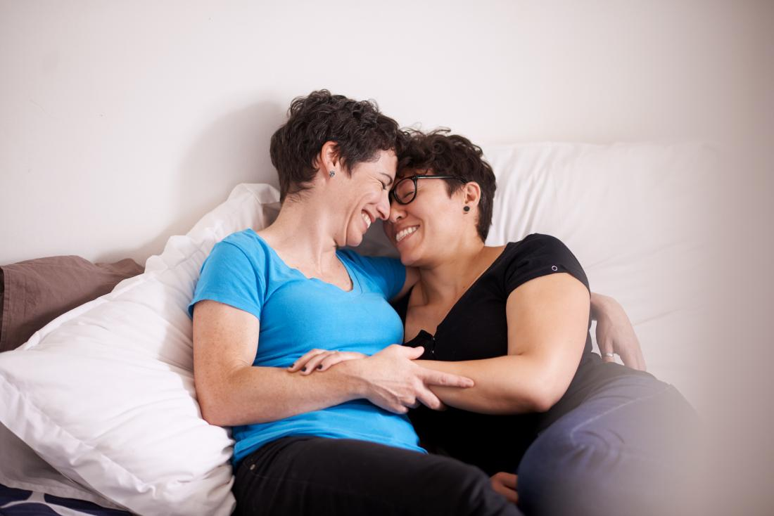 two woman having a cuddle in bed.