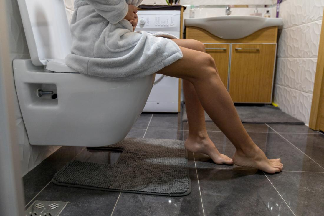 a woman in a dressing gown experiencing pain on the toilet.