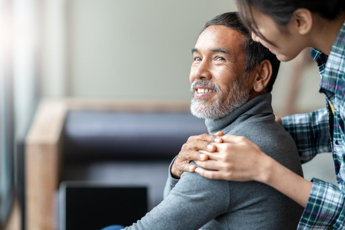a man smiling when his daughter greets him with a touch on the shoulder.
