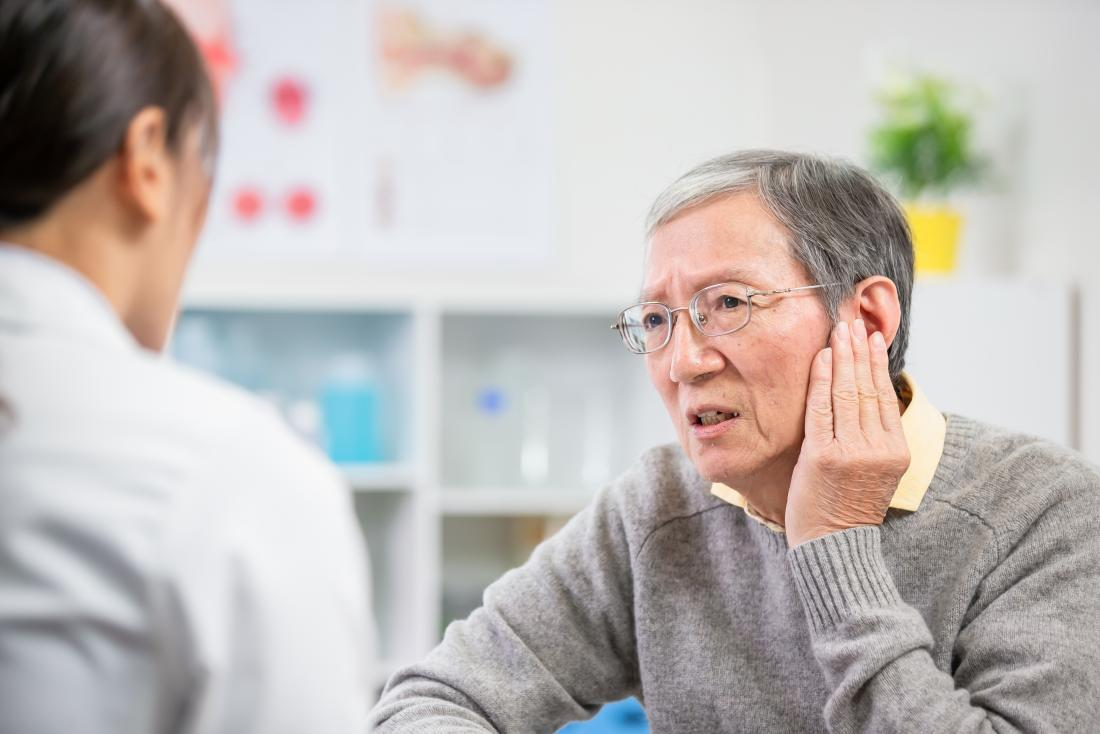 a man visiting the doctor because he is curious about the color of his earwax.