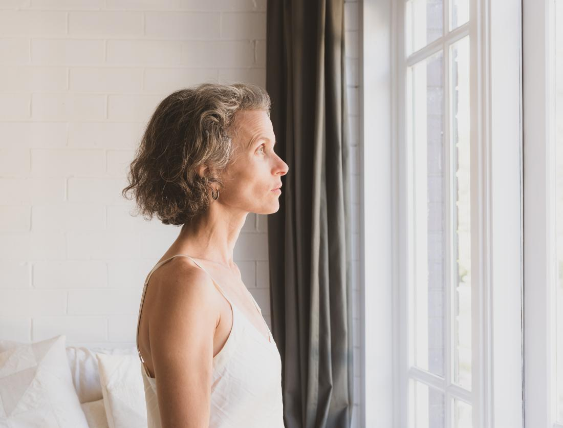 a woman looking out the window and contemplating her diagnosis of Her2 negative breast cancer