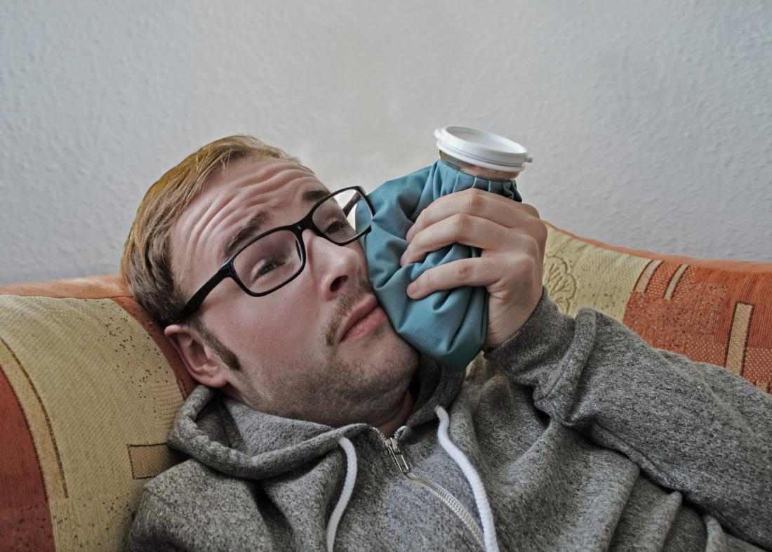 a man using a cold compress as Tooth extraction aftercare