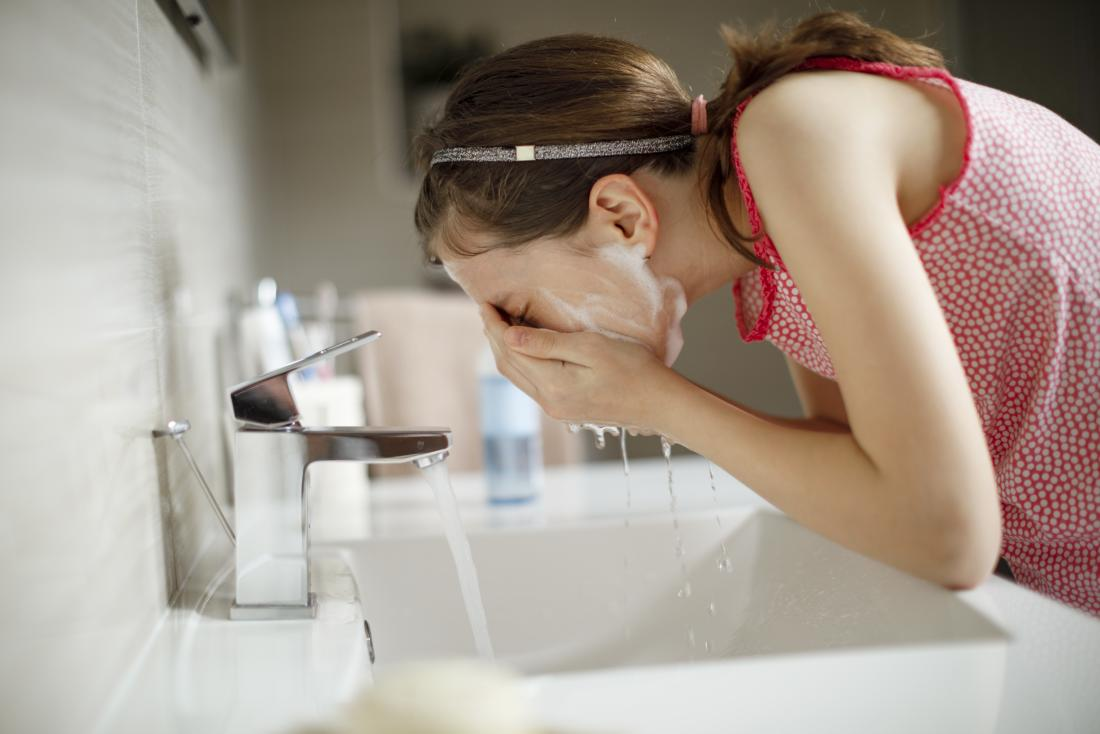 a woman applying cleanser to get rid of pimples fast