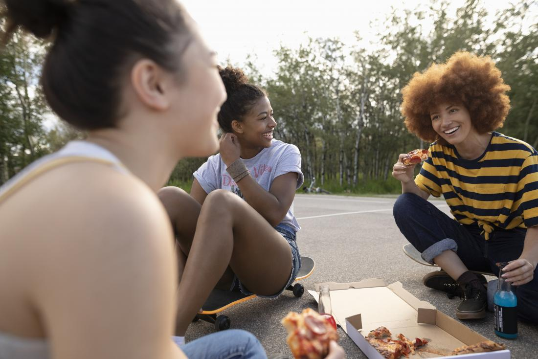 Group of young women discussing types of vaginas sitting down and eating pizza.