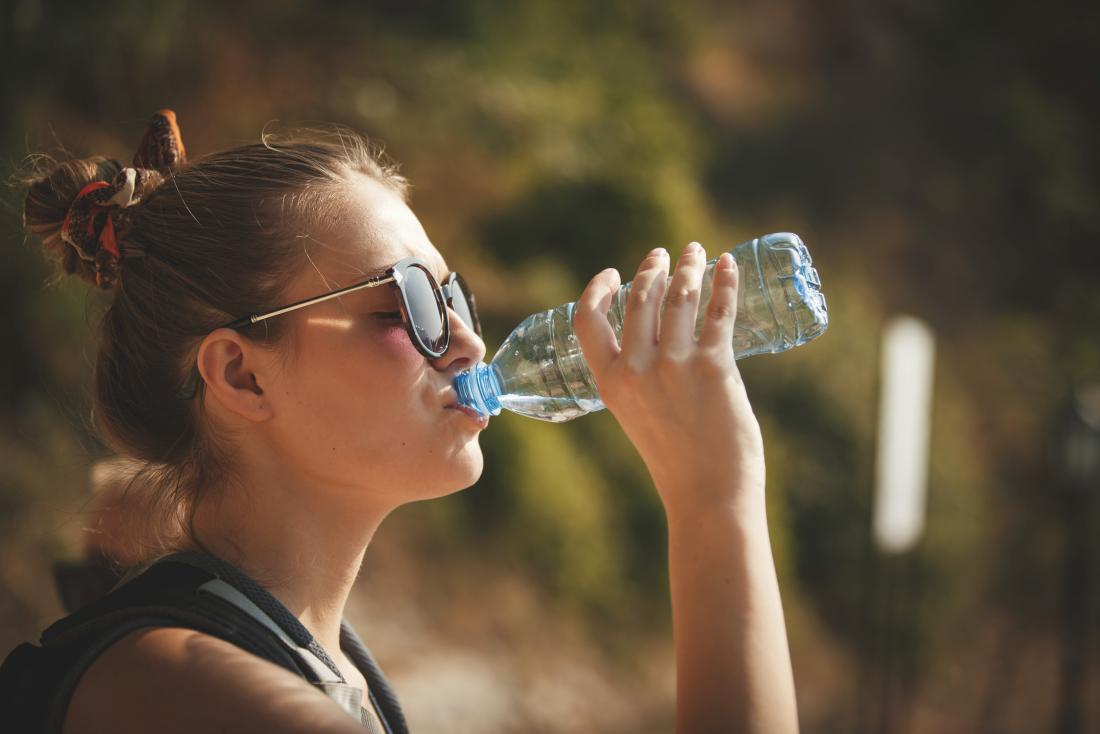 A woman drinking water as that is How to reduce body heat