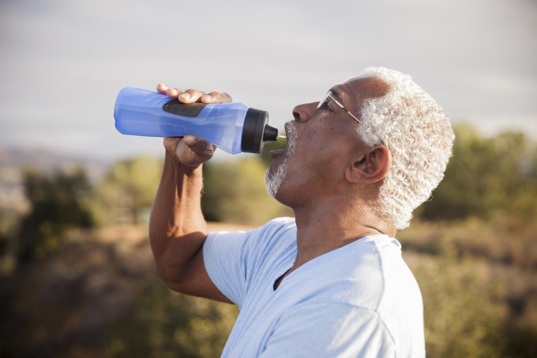 a man drinking water whilst outside on a sunny day