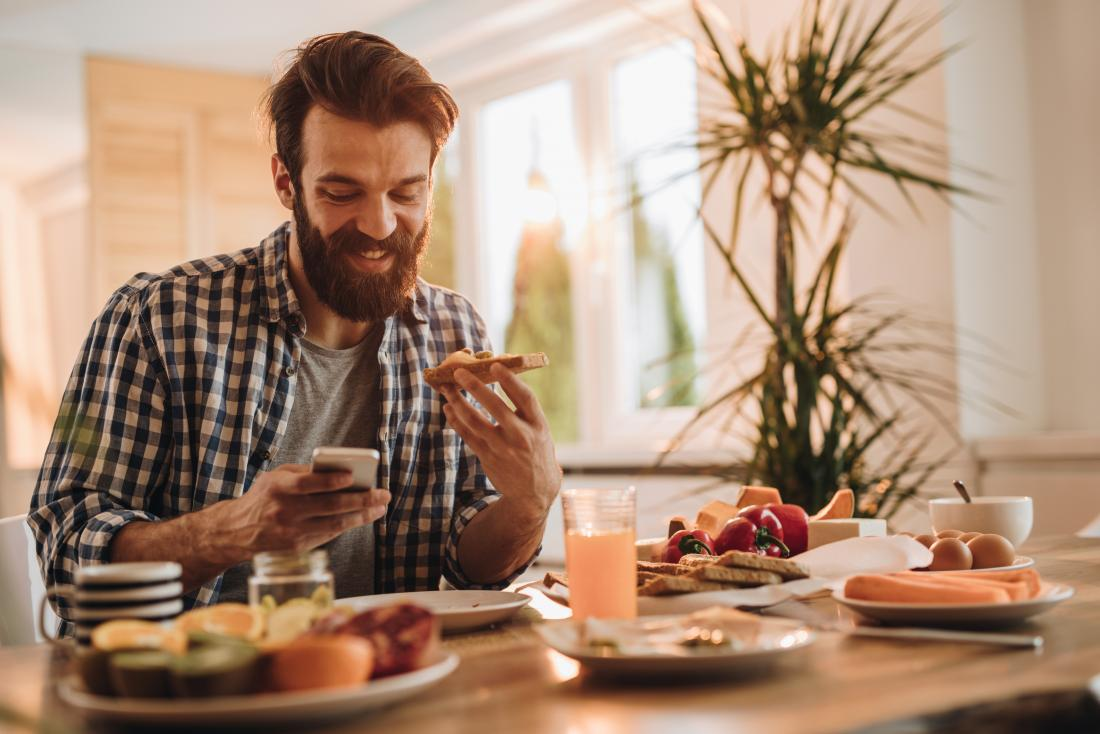 Man trying to gain weight in face eating breakfast food and looking phone