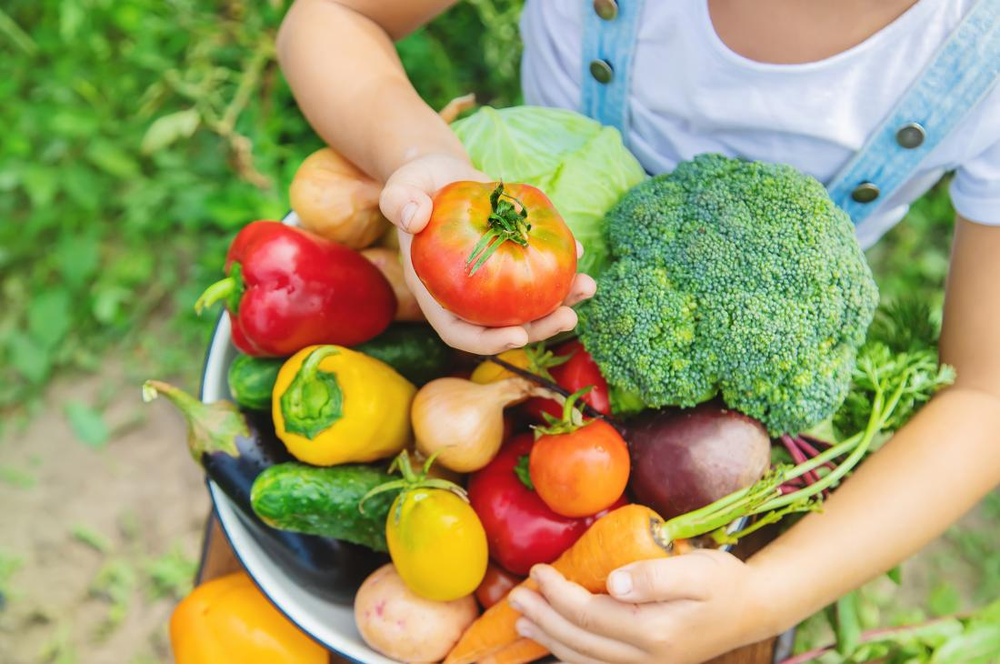 child holding fresh vegetables for hyperthyroidism diet