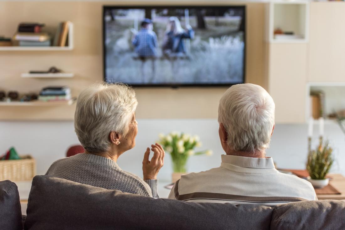 casal sênior assistindo tv no sofá