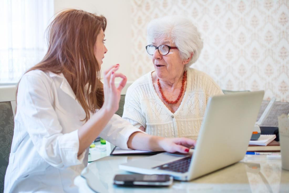 doctor explaining something to senior patient in front of laptop