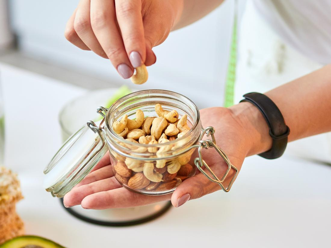 a woman about to eat nuts as part of her keto diet to lower cholesterol