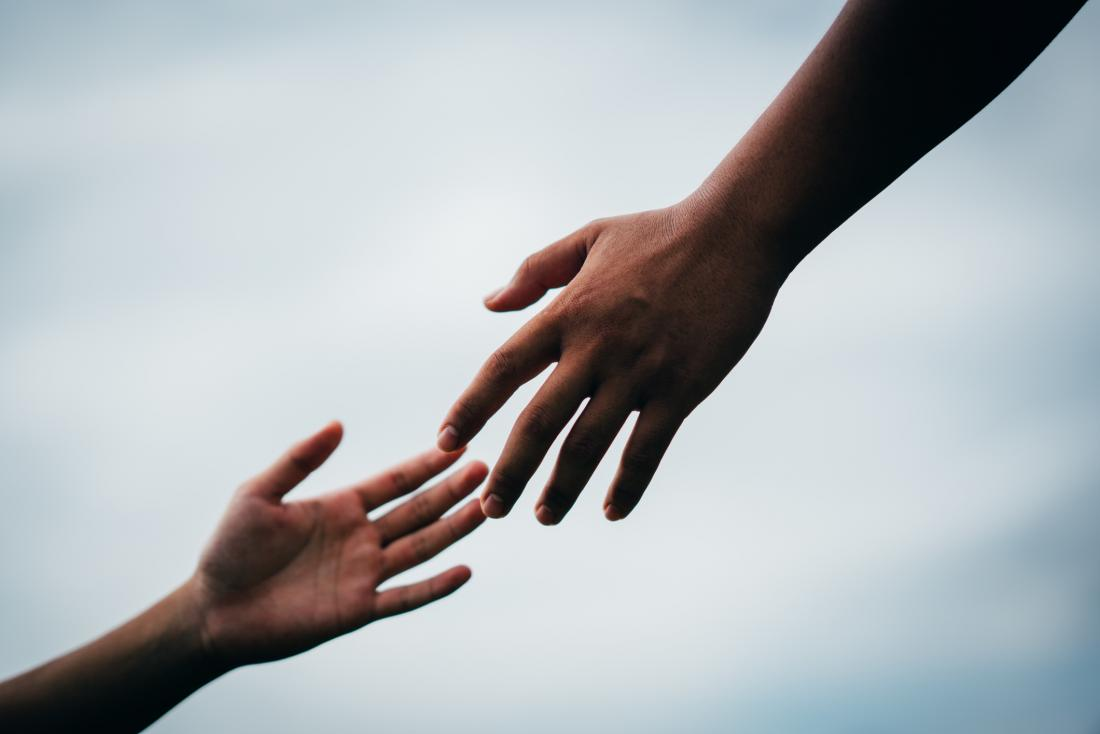 image of hand reaching to hold another hand