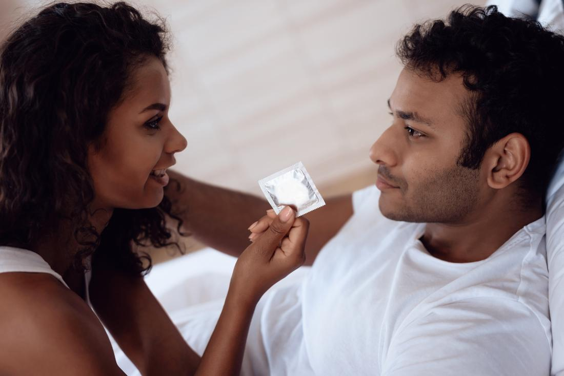 a man and woman in a bedroom with a condom that may cause Itching after sex