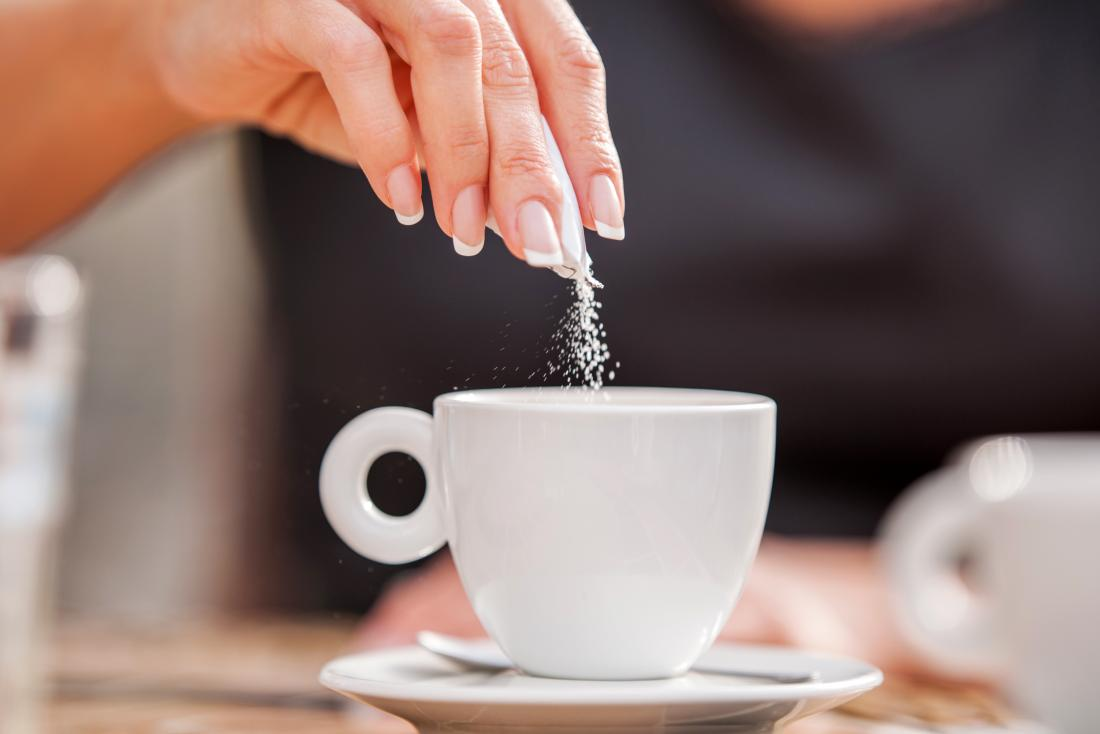 A woman putting Sugar in a cup of tea and wondering if it will cause inflammation