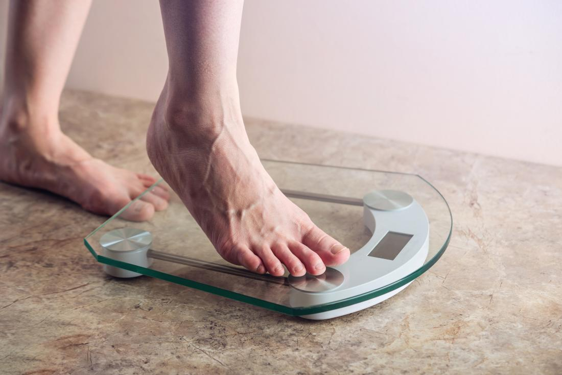 a person stepping on scales to see if they have hit a weight loss plateau