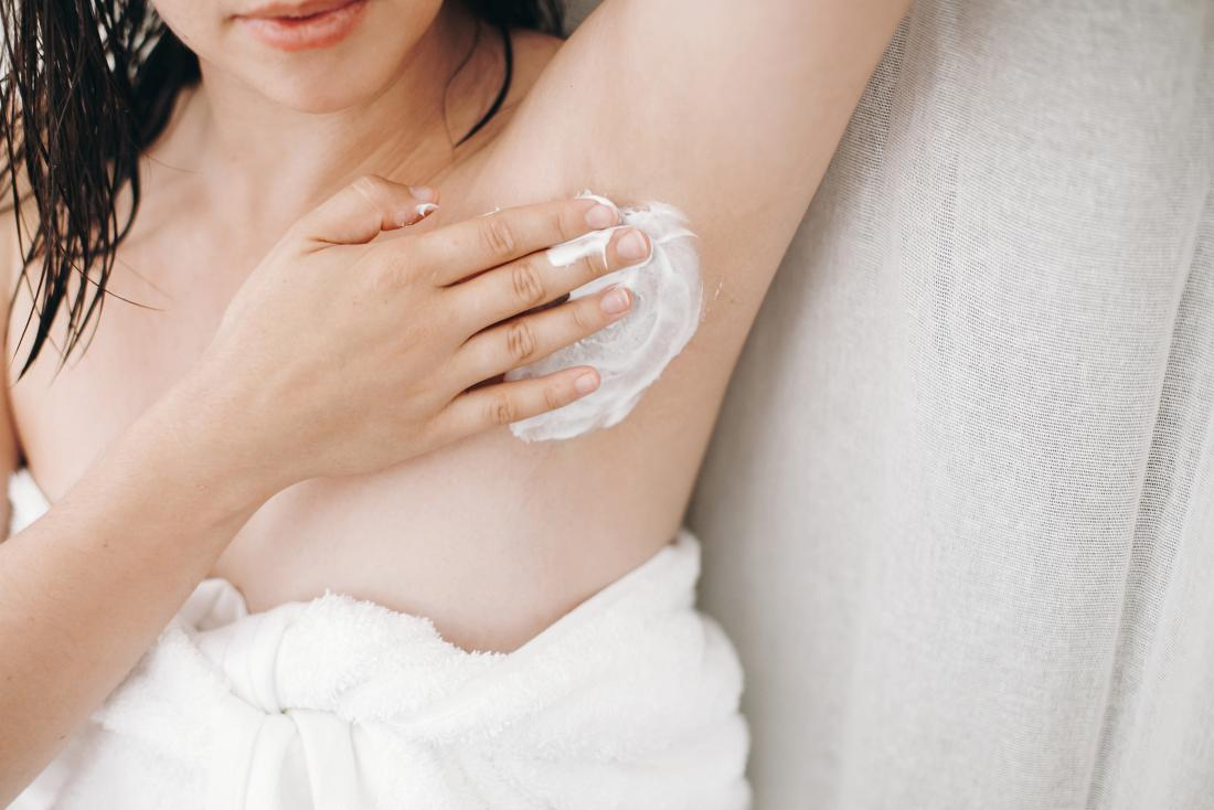 a woman applying cream . to her armpit as that is How to stop sweating