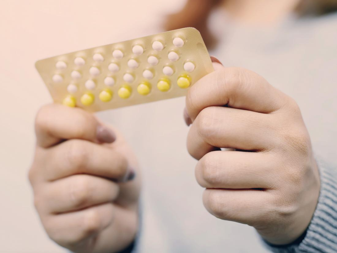 a woman holding a packet of birth control pills that she is taking for acne