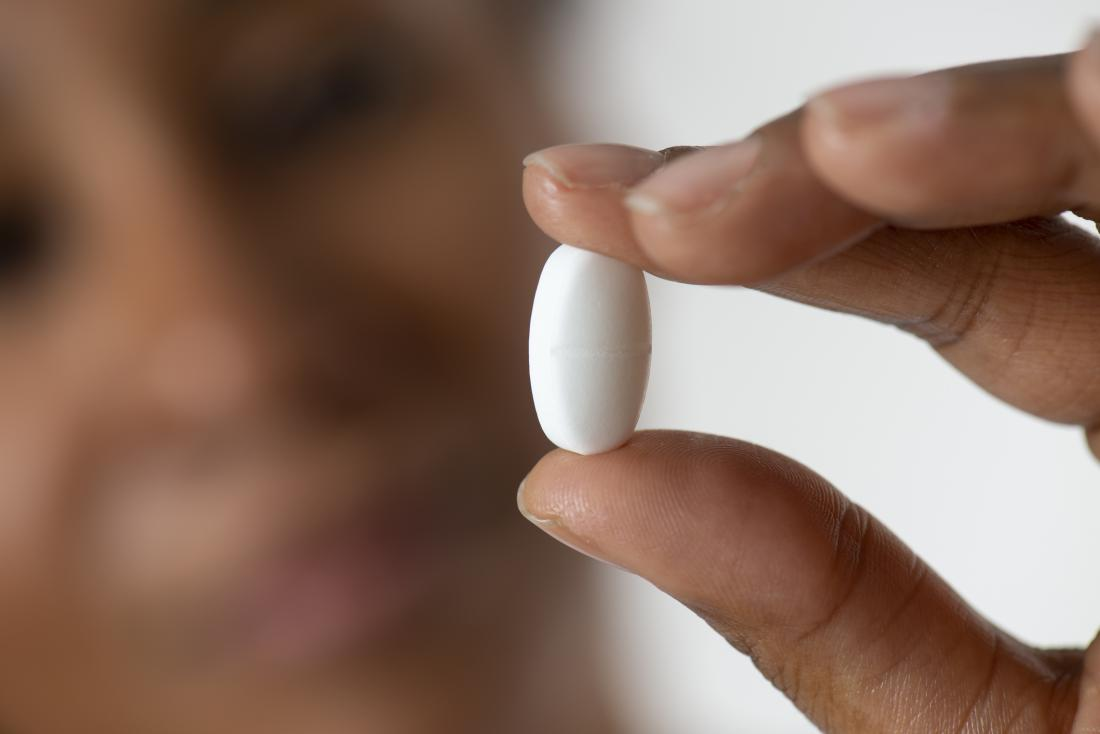 close up of woman holding white pill