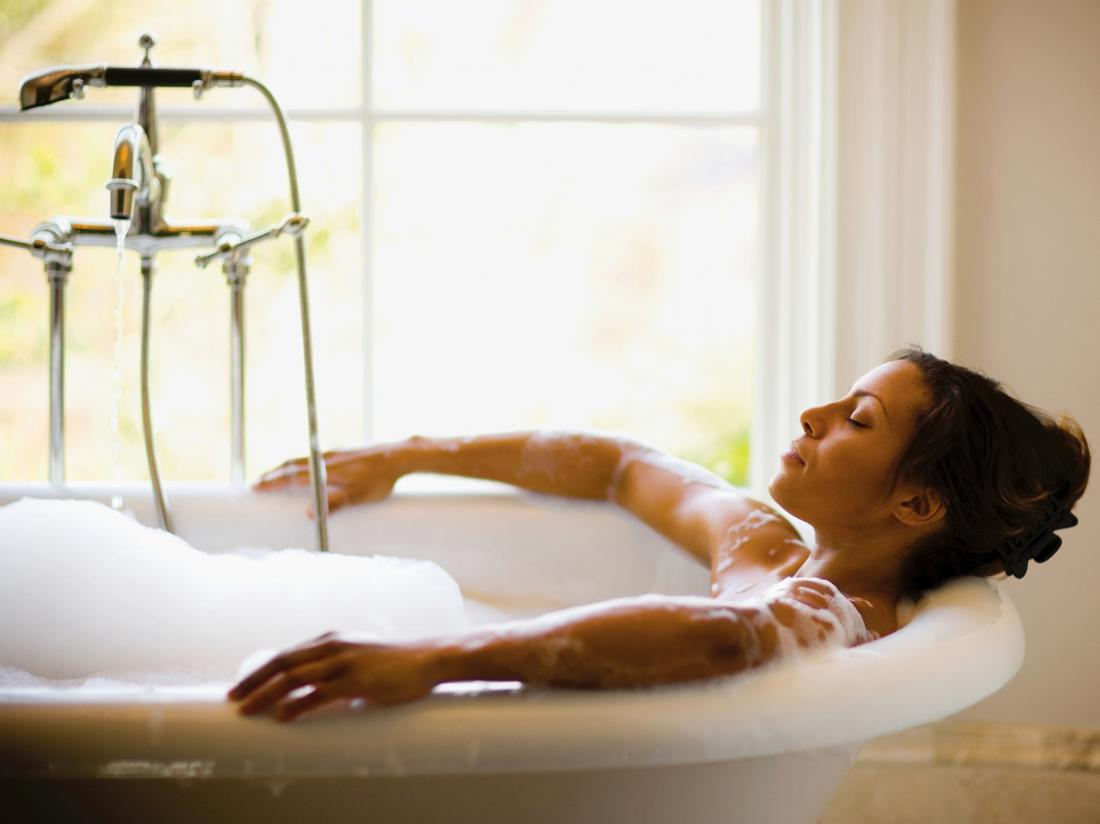 a woman in a bath tub looking very relaxed.