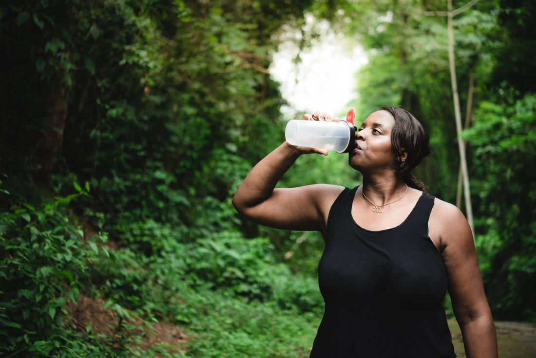 A woman drinking water during exercise as that is How to get rid of lactic acid