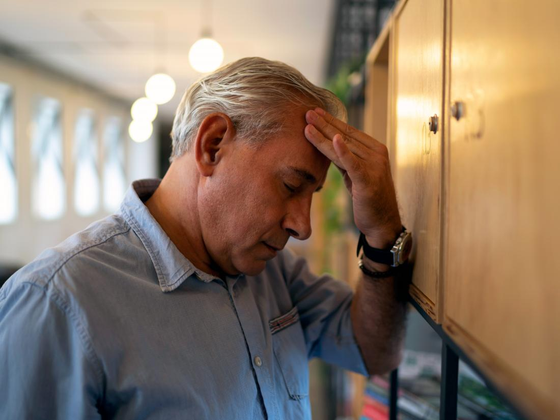 a man experiencing a headache as one of his Sugar detox symptoms