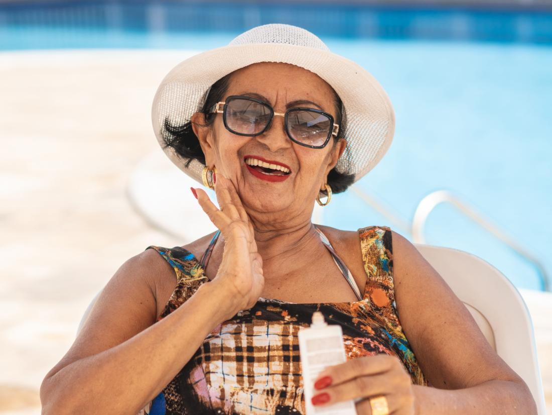 a senior lady applying sunscreen to her face.