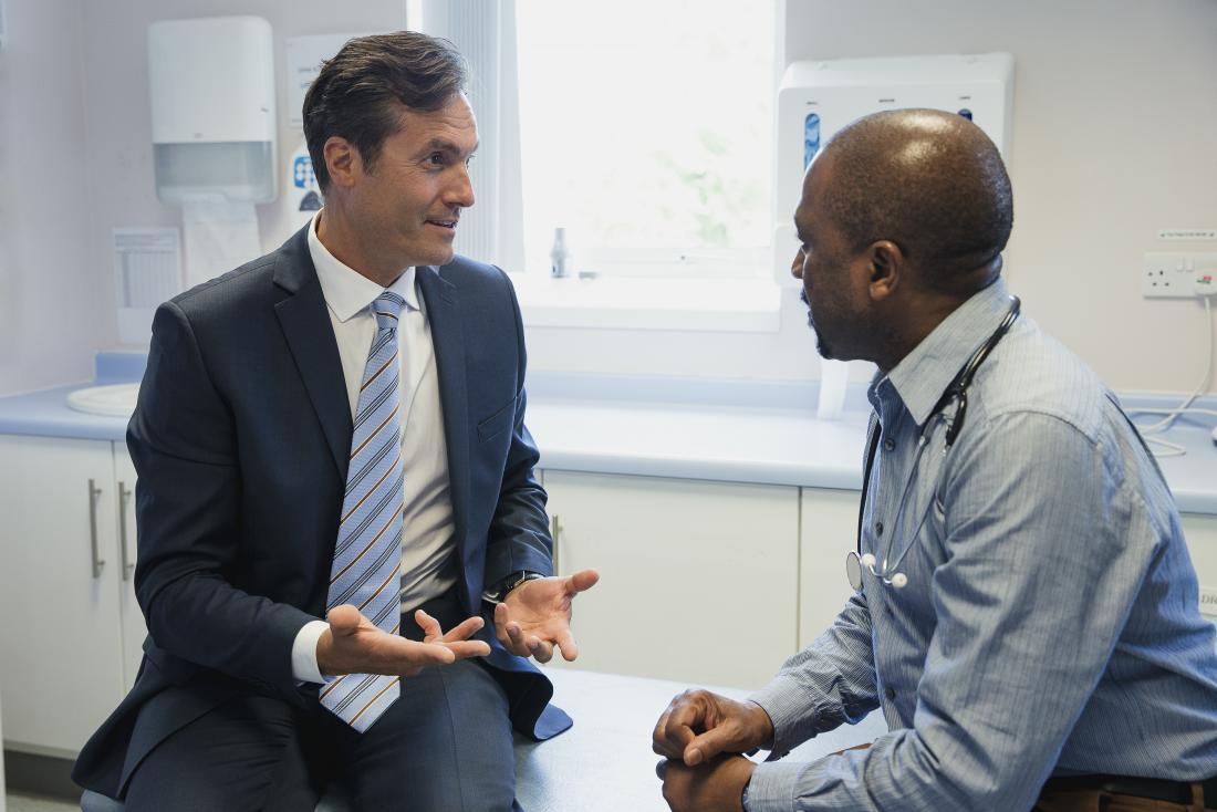 ασθενής στο γιατρό που εξηγεί τον πόνο στους όρχεις