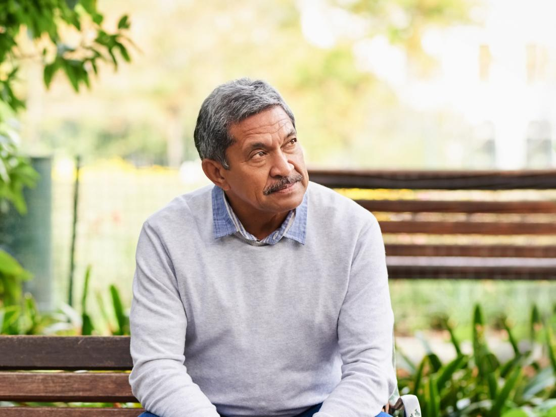 a senior man looking confused whilst sat on park bench possibly due to low levels of acetylcholine in his brain.