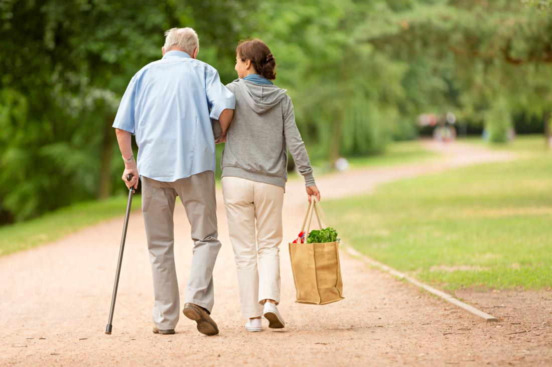 senior and carer walking slowly