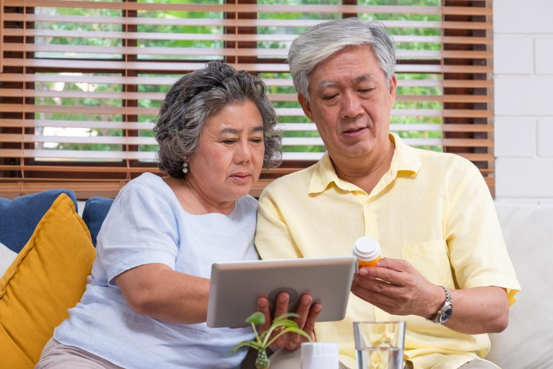 senior man and woman reading something on a tablet