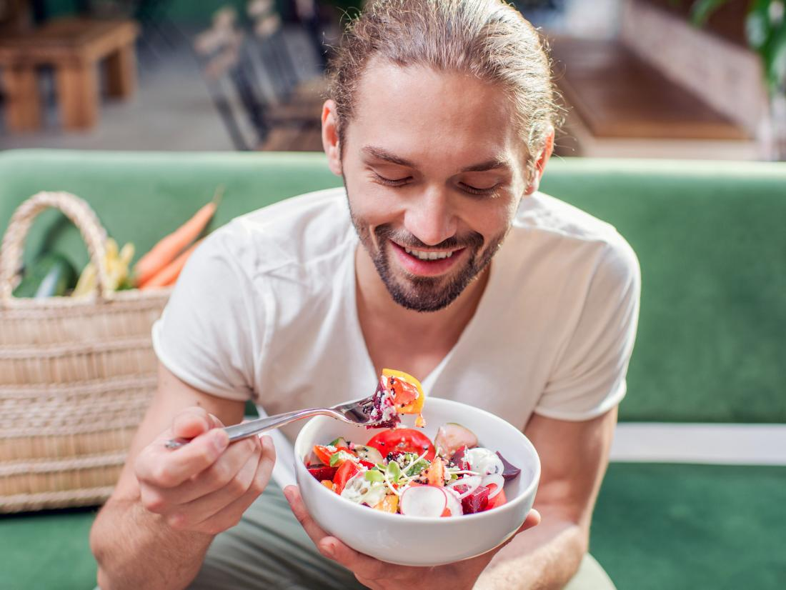 a man eating a vegan keto salad bowl.