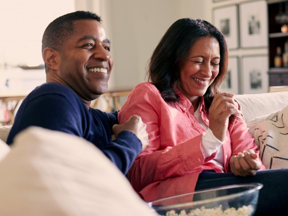 a couple looking happy on a sofa whilst the man is undergoing Vasectomy recovery