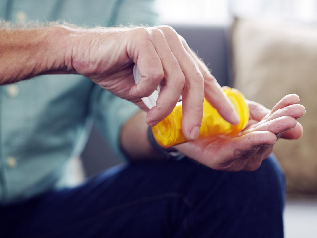 A man pouring Calcium channel blockers from a pill container into his hands.