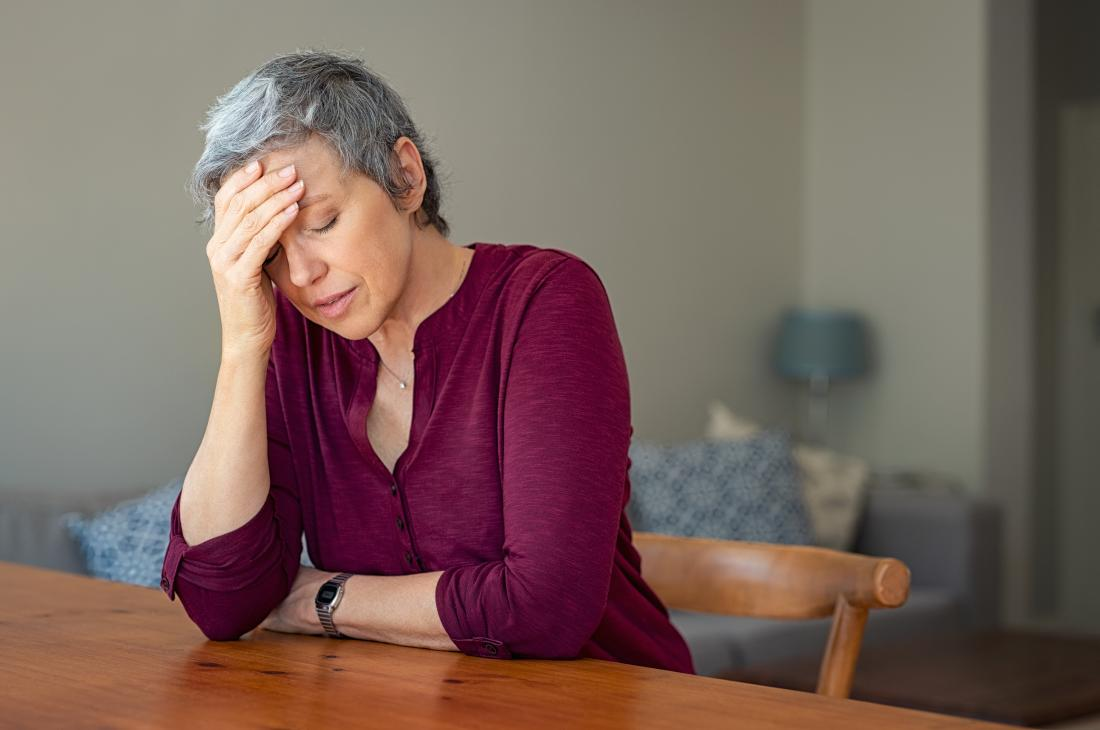 woman with a headache possibly signaling a diabetic emergency