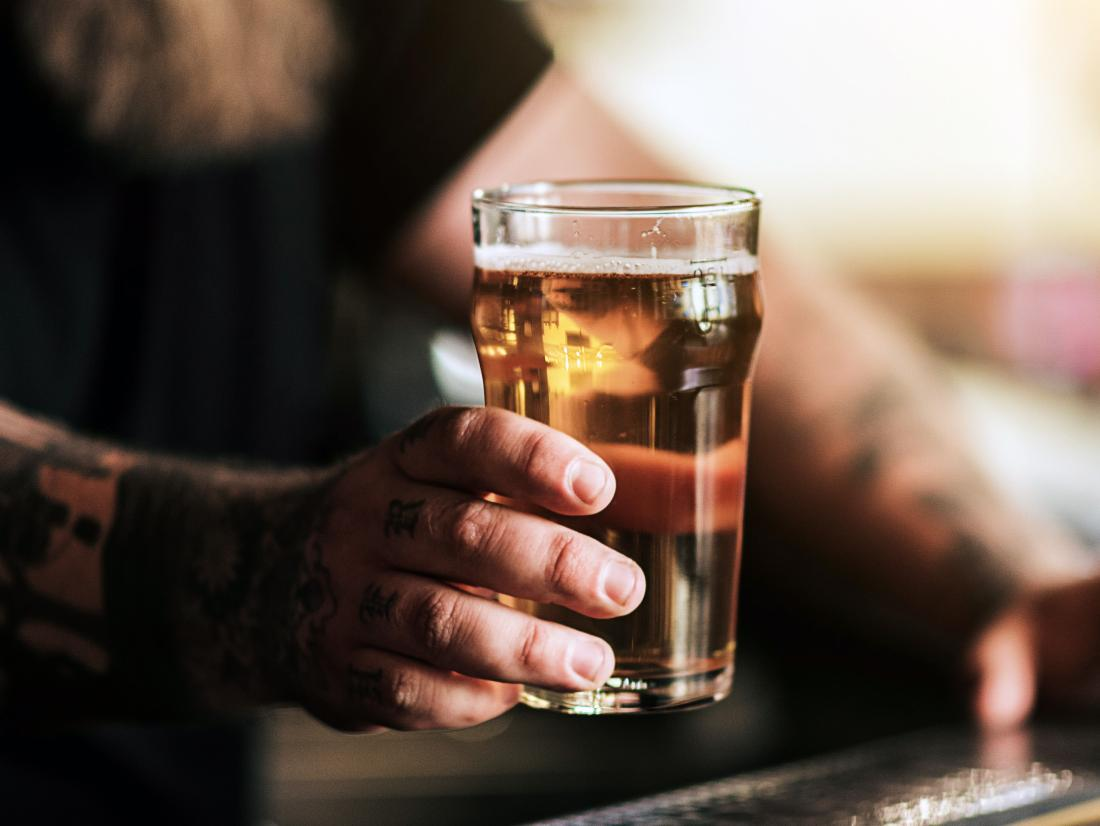 a man holding a glass of alcohol that may affect his Crohn's disease when he eats it.