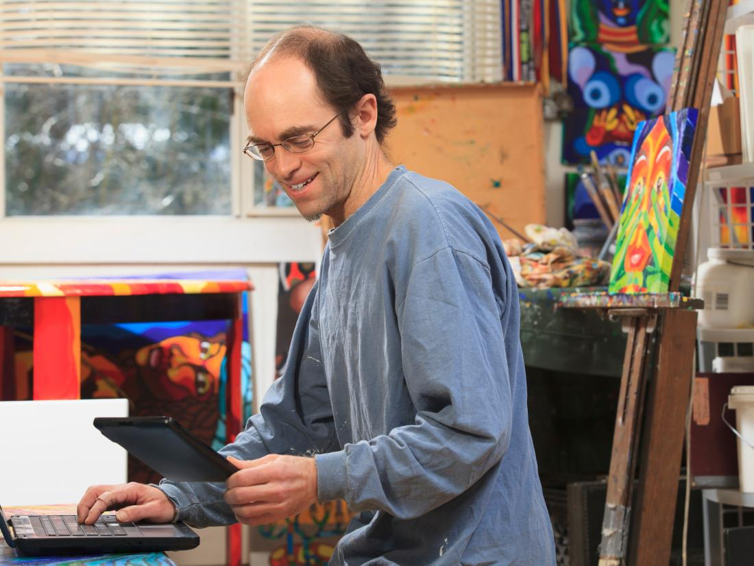 Man with Aspergers working on his tablet and computer in his art studio