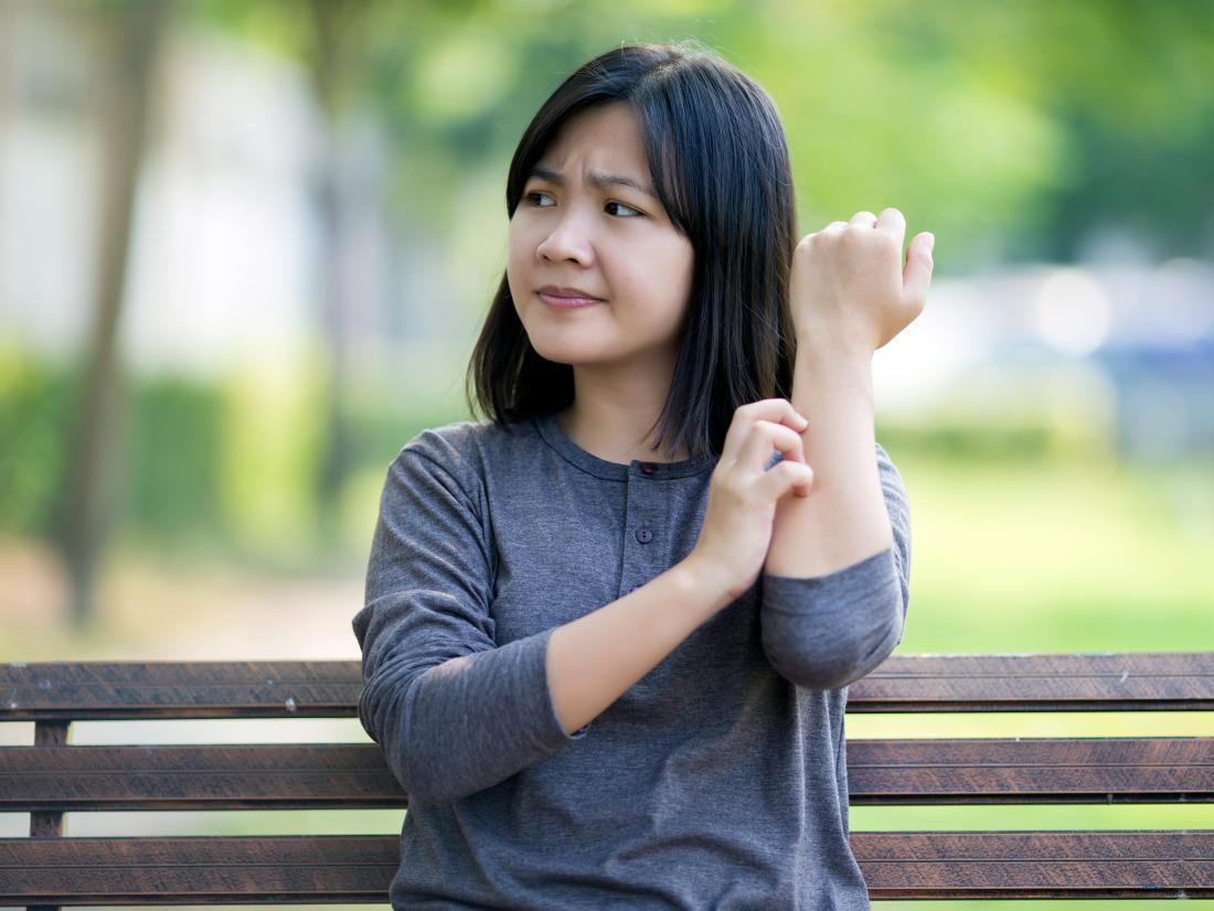 a woman scratching because of Itchy Forearms