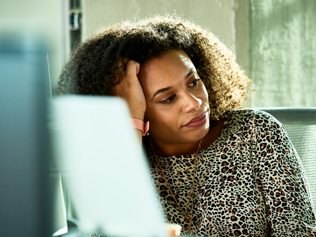 a woman looking frustrated at a work desk becasue of codeine withdrawal