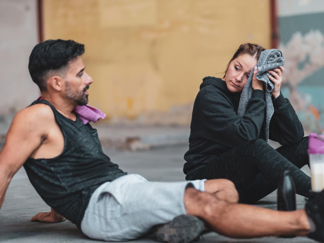 a man and woman resting after a workout.