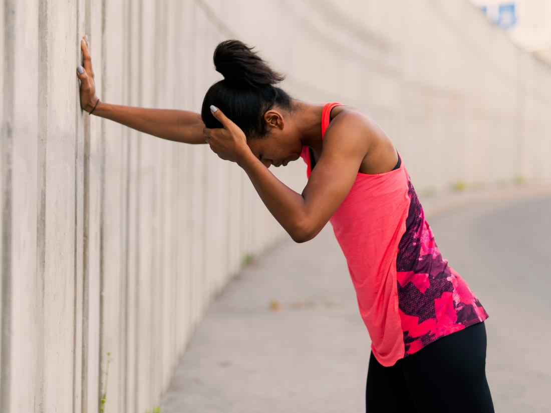 a woman jogger feeling dizzy after a workout.