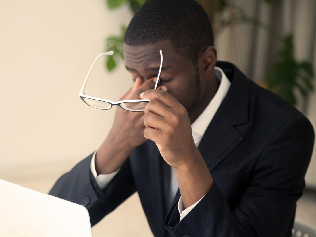 a man experiencing a headache behind the eyes because of staring at a screen for too long.